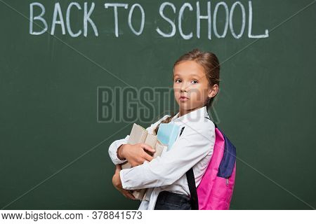 Discouraged Schoolgirl With Backpack Holding Books Near Chalkboard With Back To School Inscription