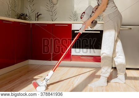 Woman Headless Cleaning House With Red Wireless Vacuum Cleaner. Red Kitchen And Sunshine In Floor. Q