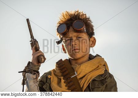 Post Apocalyptic Cyberpunk Boy With Weapon Outdoors. A Young Man Warrior In Shabby Clothes Holding G