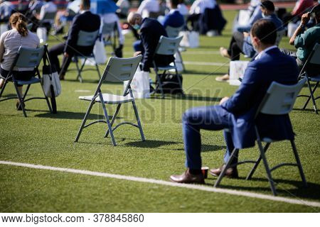People Sit On Chairs Apart One From Another To Maintain The Social Distance During The Covid-19 Outb