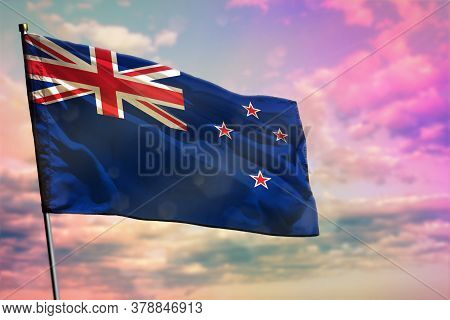 Fluttering New Zealand Flag On Colorful Cloudy Sky Background. New Zealand Prospering Concept.