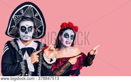 Young couple wearing mexican day of the dead costume over background pointing aside worried and nervous with both hands, concerned and surprised expression