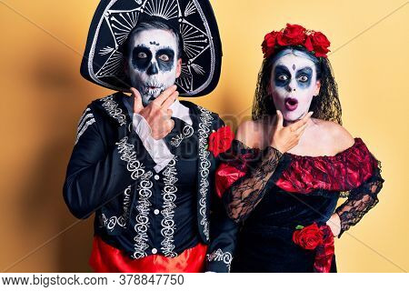 Young couple wearing mexican day of the dead costume over yellow looking fascinated with disbelief, surprise and amazed expression with hands on chin