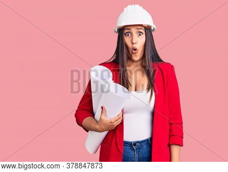 Young beautiful brunette woman wearing hardhat holding architect blueprint scared and amazed with open mouth for surprise, disbelief face