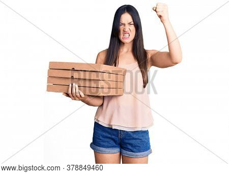 Young beautiful caucasian woman holding delivery pizza box annoyed and frustrated shouting with anger, yelling crazy with anger and hand raised