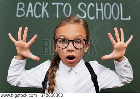 Selective Focus Of Schoolgirl In Eyeglasses Showing Scaring Gesture Near Chalkboard With Back To Sch