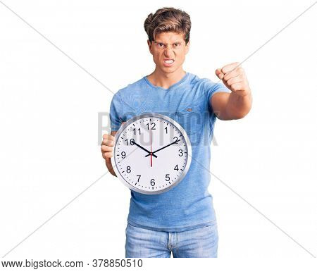 Young handsome man holding big clock annoyed and frustrated shouting with anger, yelling crazy with anger and hand raised