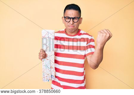 Young handsome latin man holding city map annoyed and frustrated shouting with anger, yelling crazy with anger and hand raised