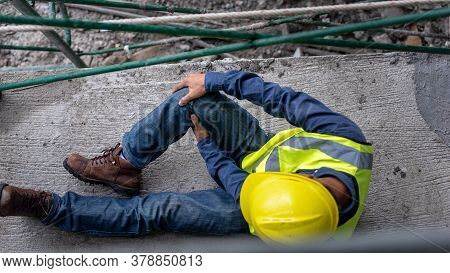 Knee Accident At Work Of Construction Worker At Site. Builder Accident Falls Scaffolding On Floor.