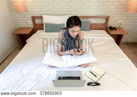 Asian Young Businesswoman Sitting The Bed Working At Home. Quarantine From Covid-19 Virus. Making On