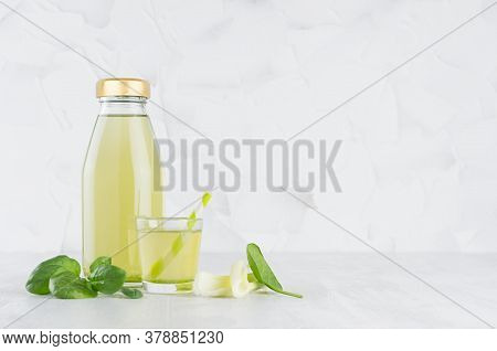 Fresh Vegetable Green Spinach And Celery Juice In Glass Bottle Mock Up With Glass, Straw, Stems, Lea