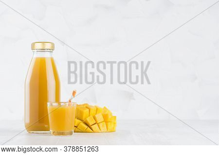 Summer Orange Pulpy Mango In Glass Bottle Mock Up With Straw, Wine Glass, Fruit Pieces On White Wood