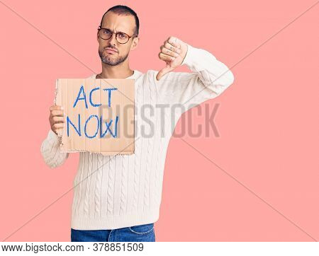 Young handsome man holding act now banner with angry face, negative sign showing dislike with thumbs down, rejection concept