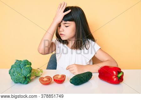 Young little girl with bang sitting on the table with veggies surprised with hand on head for mistake, remember error. forgot, bad memory concept.