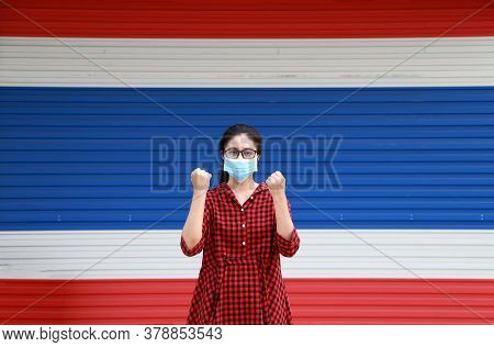 Masked Asian Woman Prevent Germs And Wear Red Plaid Dress On The Color Of Thailand Flag Door Backgro
