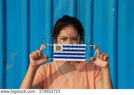 A Woman With Uruguay Flag On Hygienic Mask In Her Hand And Lifted Up The Front Face On Blue Backgrou