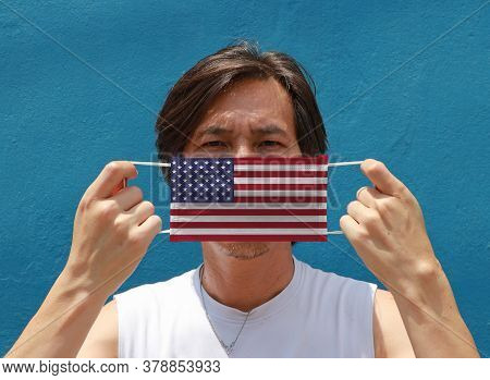 A Man With America On Hygienic Mask In His Hand And Lifted Up The Front Face On Blue Background. Tin