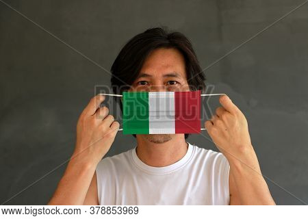 A Man With Italy Flag On Hygienic Mask In His Hand And Lifted Up The Front Face On Yellow Background