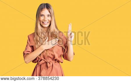 Beautiful caucasian woman with blonde hair wearing summer jumpsuit smiling swearing with hand on chest and fingers up, making a loyalty promise oath