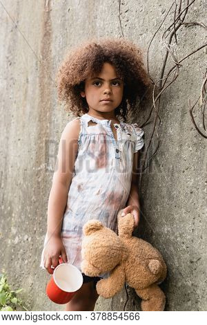 Beggar African American Child Holding Teddy Bear And Cup Near Concrete Wall On Urban Street