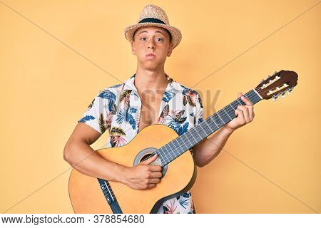 Young hispanic guy wearing summer style playing classical guitar puffing cheeks with funny face. mouth inflated with air, catching air.