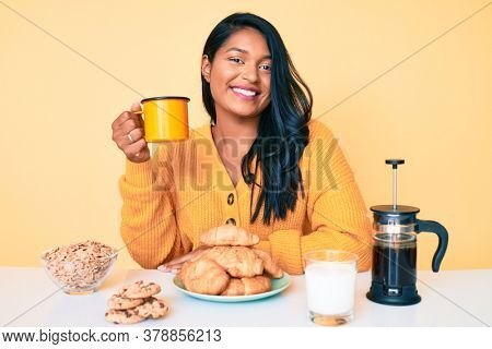 Beautiful latin young woman with long hair sitting on the table having breakfast looking positive and happy standing and smiling with a confident smile showing teeth