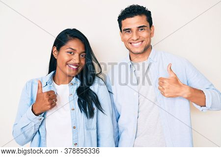 Beautiful latin young couple wearing casual clothes doing happy thumbs up gesture with hand. approving expression looking at the camera showing success.