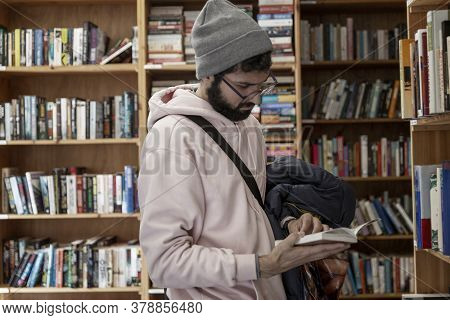 Young Man In A Bookstore. A Brunette With Glasses And A Hat Holds A Book In Her Hands. Education, Sc
