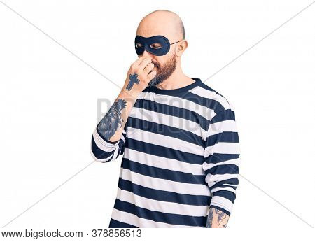 Young handsome man wearing burglar mask smelling something stinky and disgusting, intolerable smell, holding breath with fingers on nose. bad smell