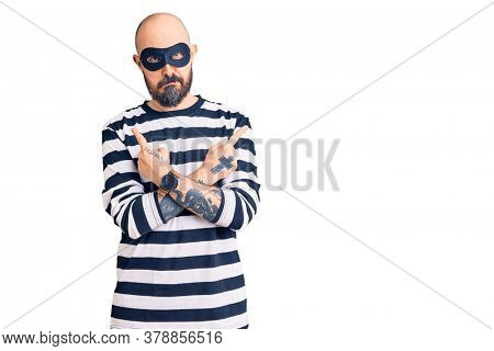 Young handsome man wearing burglar mask pointing to both sides with fingers, different direction disagree