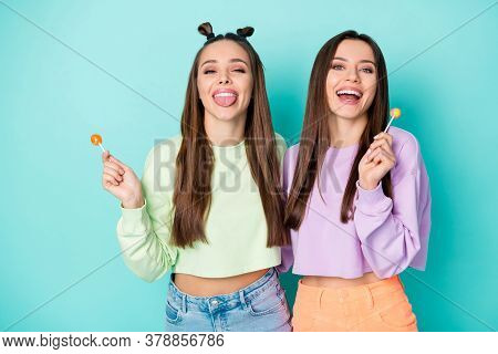 Photo Of Two Funny Lady Hold Lollipop Chupa Chups Hands Sweets Addicted Stick Tongue Out Mouth Wear