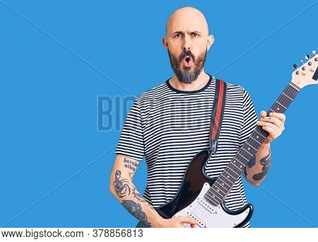 Young handsome man playing electric guitar scared and amazed with open mouth for surprise, disbelief face