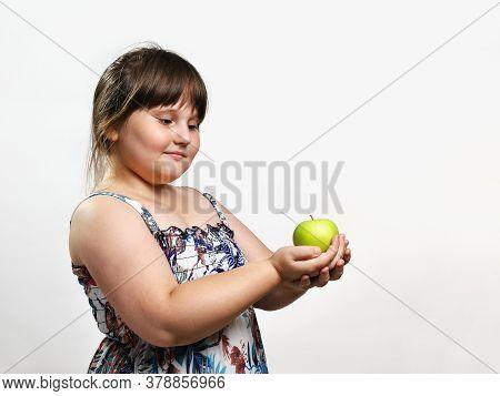 Little Chubby Smiling Girl Holding Green Apple In Her Hands. Half-length Portrait On Light Backgroun