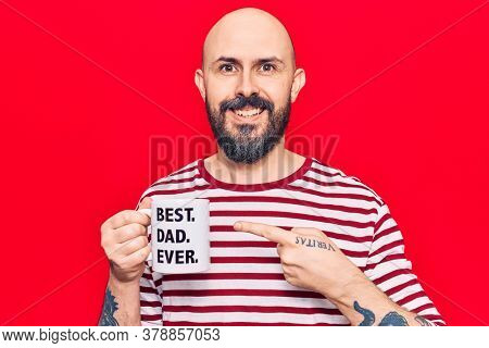 Young handsome man drinking mug of coffe with best dad ever message smiling happy pointing with hand and finger