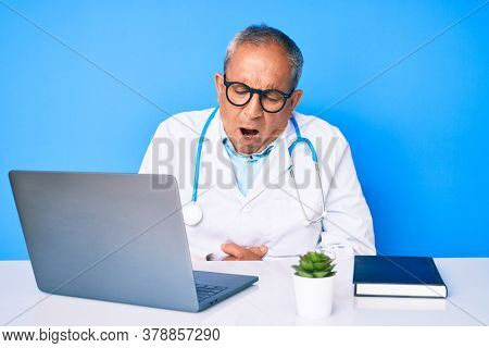 Senior handsome man with gray hair wearing doctor uniform working using computer laptop with hand on stomach because indigestion, painful illness feeling unwell. ache concept.
