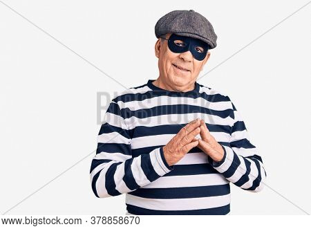 Senior handsome man wearing burglar mask and t-shirt hands together and fingers crossed smiling relaxed and cheerful. success and optimistic