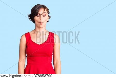 Beautiful young woman with short hair wearing casual style with sleeveless shirt making fish face with lips, crazy and comical gesture. funny expression.