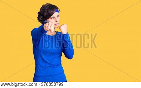 Beautiful young woman with short hair wearing training workout clothes punching fist to fight, aggressive and angry attack, threat and violence