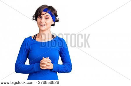 Beautiful young woman with short hair wearing training workout clothes with hands together and crossed fingers smiling relaxed and cheerful. success and optimistic
