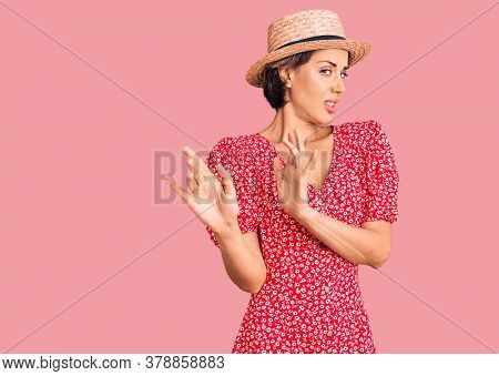 Young beautiful woman wearing summer hat disgusted expression, displeased and fearful doing disgust face because aversion reaction. with hands raised