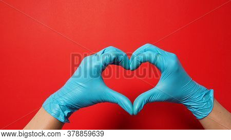 A Hand Is Doing Heart Or Love Hand Sign And Wear Blue Surgical Gloves Or Latex Gloves On Red Backgro