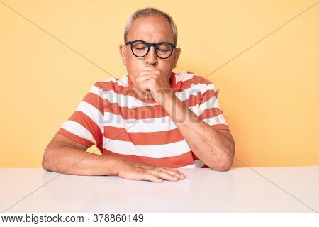 Senior handsome man with gray hair wearing casual clothes and glasses feeling unwell and coughing as symptom for cold or bronchitis. health care concept.