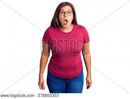 Middle age latin woman wearing casual clothes and glasses scared and amazed with open mouth for surprise, disbelief face