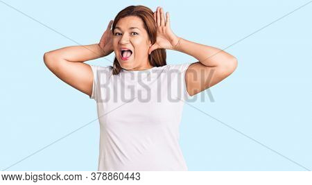 Middle age latin woman wearing casual white tshirt smiling cheerful playing peek a boo with hands showing face. surprised and exited