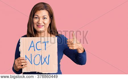Middle age latin woman holding act now banner smiling happy and positive, thumb up doing excellent and approval sign