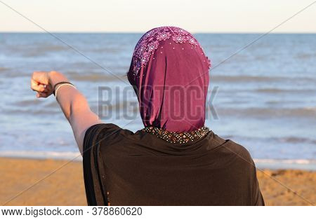 Woman With Veil On Her Head By The Sea While Pointing To A Point Towards The Water