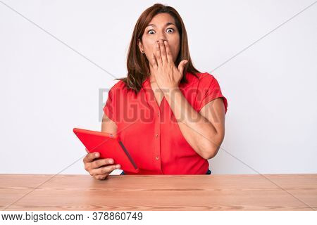 Middle age brunette hispanic woman using touchpad sitting on the table covering mouth with hand, shocked and afraid for mistake. surprised expression