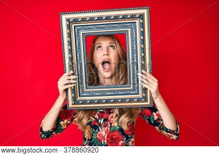 Young caucasian woman with blond hair holding empty frame angry and mad screaming frustrated and furious, shouting with anger looking up.