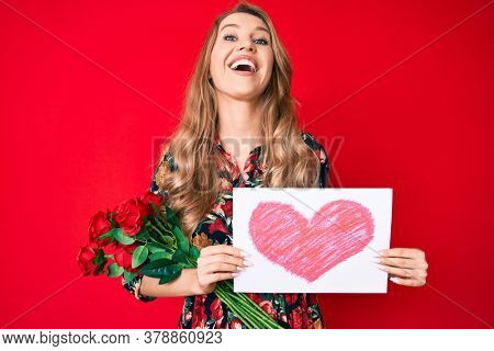 Young caucasian woman with blond hair holding heart draw smiling and laughing hard out loud because funny crazy joke.