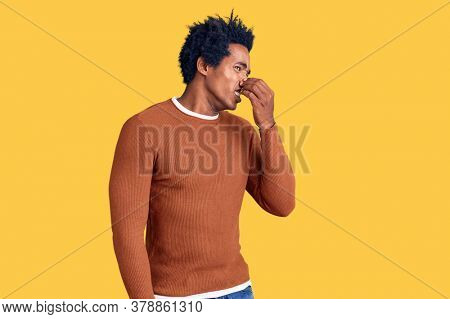 Handsome african american man with afro hair wearing casual clothes smelling something stinky and disgusting, intolerable smell, holding breath with fingers on nose. bad smell